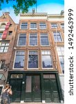 Small photo of Amsterdam, North Holland / Netherlands - June 22nd, 2019: A young girl taking a picture in front of the Anne Frank House