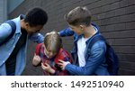 Small photo of Cruel teenagers punching younger boy, physical intimidation, school bullying