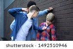 Small photo of Cruel students threatening to punch junior boy, school bullying, intimidation