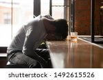 Depressed drunk young addicted man drinker sleeping alone on bar counter with whiskey glass, sad guy alcoholic passed out after drink too much alcohol addiction abuse, intoxication alcoholism concept