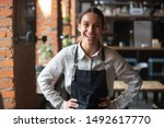 Small photo of Cheerful young waitress wearing apron laughing looking at camera, happy businesswoman small business owner of girl entrepreneur cafe employee posing in restaurant coffee shop interior, portrait