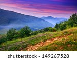 view of the mountains in the fog in the morning standing on a hillside - stock photo