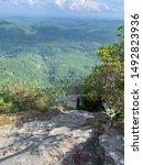 Small photo of Standing on the rocks overlooking a cliff on a hiking trip up Whiteside Mountain in the beautifully green Appalachian Mountains.