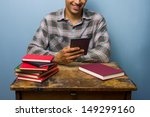 Small photo of Young man prefers his e-reader to books