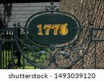 1775 year sign on metal forging fence in front of big tree. Information table placard or signboard in park or botanic garden to designate remarkable date or event