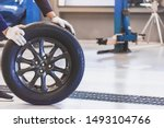 Small photo of Asian man mechanic inspection service maintenance car holding tyre or tire car inspection for Measure quantity Inflated Rubber tires car.Close up hand push wheel to for tyre pressure automotive