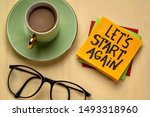 Small photo of let us start again motivational reminder note with a cup of coffee, determination and tenacity concept