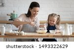 Small photo of Pretty woman and little adorable daughter sitting at table in kitchen cook together stirring eggs for pie, cookies or pancakes, teach kid recipes, embodiment of ideal wife of mom and housewife concept