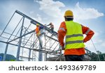 Engineer technician watching team of workers on high steel platform,Engineer technician Looking Up and Analyzing an Unfinished Construction Project. - stock photo