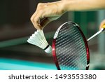 Small photo of Hands of BADMINTON player holding racket serving white new shuttlecock with blur Badminton court background, popular indoor sport concept