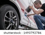 Caucasian Technician Trying To Fix RV Travel Trailer Electric Hookup Problem Looking Inside Outside Compartment. - stock photo