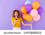Small photo of Image of happy young woman celebrating birthday with multicolored air balloons and piece of pie isolated over violet background