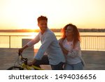 Young couple riding bicycle on city waterfront at sunset