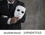 Small photo of Businessman holding white mask in his hand dishonest cheating agreement.Faking and betray business partnership concept