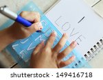 Small photo of Child's hands writing a message on a paper using a stencil