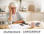 Small photo of Sad frustrated senior woman pensioner having depressed look, holding hand on her face, calculating family budget, sitting at kitchen counter with laptop, papers, coffee, calculator and cell phone