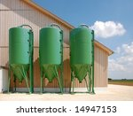 Battery of green silos on an agriculture site - stock photo