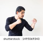Small photo of Asian man doing fighting stance. Young man with box stance ready to fight. Aggressive young man with a goatee standing in a fight stance, fists raised, strong and confident.