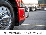 Big rig red heavy-duty powerful semi truck wheel with aluminum rim and shiny tire and chrome grille guard standing on the truck stop parking lot in dedicated spot - stock photo