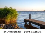Beautiful tranquil waterscape in warm sunset light in Friesland, The Netherlands. Rocks and reeds on the left, and a scaffolding on the right, showing water and a landscape horizon in the background .