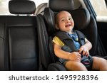 Small photo of Portrait of happy little child sitting in car seat with safety belt, enjoying road trip. Cute baby boy smiling and having fun while being in the infant car seat. Toddler enjoying travel, copy space.