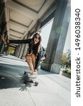 Small photo of Beautiful young skater woman riding on her longboard in the city. Stylish girl in street clothes rides on a longboard.