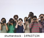 Group of multiethnic people taking photos straight at the camera in studio