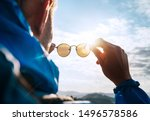Small photo of Backpacker man looking at bright sun through polarized sunglasses enjoying mountain landscape. Eye & Vision Care human health concept image.