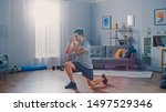 Small photo of Strong Athletic Fit Man in T-shirt and Shorts is Doing Forward Lunge Exercises at Home in His Spacious and Bright Apartment with Minimalistic Interior.