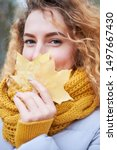 Small photo of Redhead curly cheerful girl with beautiful blue eyes wearing trendy autum color sweater and scarf holding yellow maple leaves near face. Autumntime. Portrait.