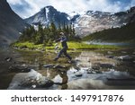 Young adventure healthy woman is hiking Mount Fitzwilliam trail in Jasper National park,  Alberta, Canada. Solo woman traveling backpacker jumping in the lake