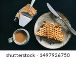 Waffles with brown cheese (brunost) / Traditional Norwegian breakfast served on ceramic pottery plate with mug of steaming hot coffee