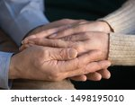Small photo of Close up elderly husband holding his wife wrinkled hands, supporting, caring, expressing love and mutual understanding, tenderness, senior man comforting old woman, married couple compassion.