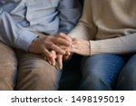 Small photo of Close up elder family couple sitting on sofa, holding hands, old loving married man supporting wife, mutual understanding, psychological help, comforting, taking care of each other.