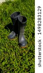 Small photo of Child's black work boots / mud boots in green grass on sunny day.