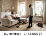 Small photo of Young african American wife relax on couch in living room drinking wine, biracial husband clean house carpet with vacuum cleaner, mixed race couple share household chores, family role reversal concept