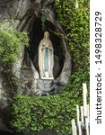 Small photo of Statue of Our Lady of Immaculate Conception with a rosary in the Grotto of Massabielle in Lourdes, France