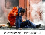 Small photo of Selective focus firefighter in fire suit on safety rescue duty help a man suffocating smoke in burning premises by first aid emergency and carry him to outside. Safety, rescue and health care concept.