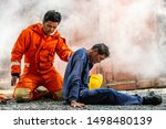 Small photo of Selective focus medium shot of firefighter man in fire suit on safety rescue duty help a man suffocating smoke inside burning premises by first aid emergency. Safety, rescue and health care concept.