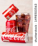 Small photo of LONDON, UK - AUGUST 03, 2018: Aluminium tins and original glass of Original Coca Cola soft drink on wood. Most popular drink in the world.