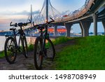 Small photo of Bicycles at sunset. Two bicycles under the expressway. Concept - Bicycle Benefits. Shorten the path. Bikes under the bridge. Accessories for bikes. Triathlon. Sale of bicycles. Alternative road.