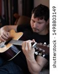 Small photo of vertical portrait of a young man in black t-shirt playing an acoustic guitar. Focus is on his hand holding a chord string for a chord