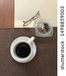 Small photo of Cup of coffee morning with cigarette astray and reading glass top view