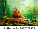 Stock photo halloween party burger in shape of scary pumpkin on natural wooden board halloween food concept 1499027513