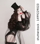 Small photo of Brunette woman with red lips in black top hat. Girl with brown hair and pale skin. Brunette woman in black fetish lingerie. Long wavy wig. Voluminous hair. Retro lady in vintage fetish clothes
