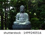 A Buddha statue surrounded by trees on the grounds of Sensoji (Asakusa Kannon Temple), a Buddhist temple in Asakusa, Tokyo, Japan, photographed in summer