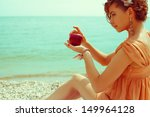 Happy honeymoon concept. Young girl in trendy vintage dress sitting on the beach and holding a red apple - love symbol. Sunny summer day. Copy-space. Outdoor shot - stock photo