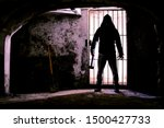 Small photo of Scary dark man holding hammer inside dungeon - Silhouette of serial killer standing in creepy prison with threatening attitude - Concept of madness and murder - Backlight image with enhanced contrast