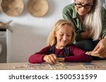 Small photo of Grandmother and granddaughter doing puzzle together at home. Senior woman helping smiling little girl to solve puzzles. Happy grandchild solving puzzle at home while mature granny, playing together.