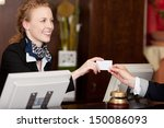 Stock photo smiling stylish beautiful receptionist handing over a blank white card to a client at the reception 150086093